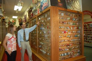 Man showing Hallmark Ornament museum display to girl next to him
