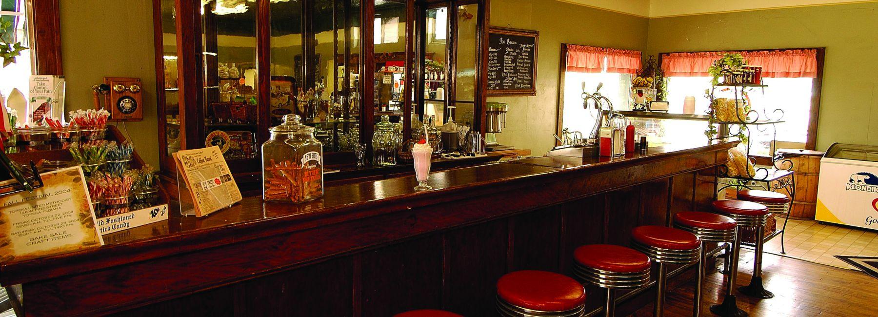 Red stools at the bar at Emma's cafe