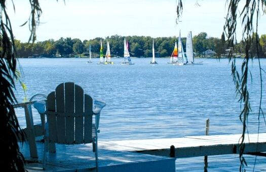 An adirondack chair sits on a dock looking out on sailboats on a lake.