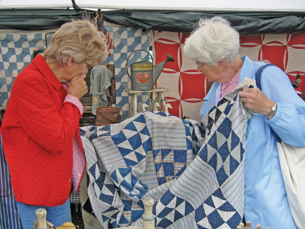 Two women look at the pattern of a quilt at Shipshewana Antique Market